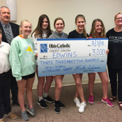 group of students holding giant check